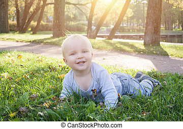 Happy little baby boy lying on the green grass outdoor (child 1,5 years old)