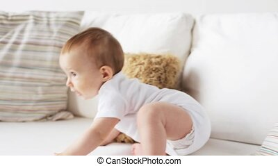 happy little baby crawling along sofa at home 7