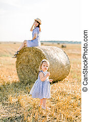 Happy little baby girl in wheat field with hay bales on warm and sunny summer evening, holding wheat spikelets, while her pretty mother in straw hat and dress sitting on hay stack on the background