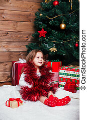 Happy little baby girl playing with garland near Christmas tree at home