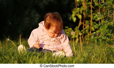 Happy little baby-girl seated on the green grass in the park...