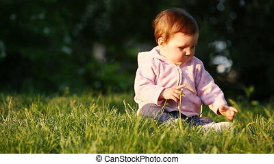 Happy little baby-girl seated on the green grass in the park at sunset.