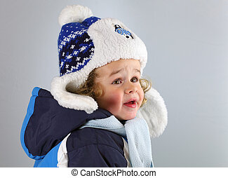 Happy little baby in a huge fur hat on white blackground