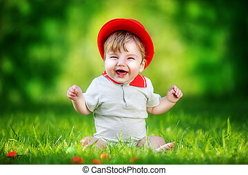 Happy little baby in red hat having fun in the park on solar...