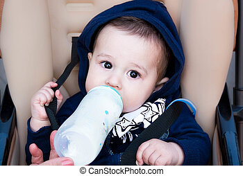 happy little baby sitting in a stroller and drinking from bottle of milk, in winter clothes, the concept food breast .