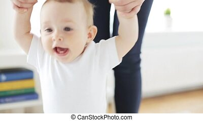 happy little baby walking with mother help at home 14