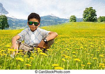 Happy little black sitting boy in sunglasses