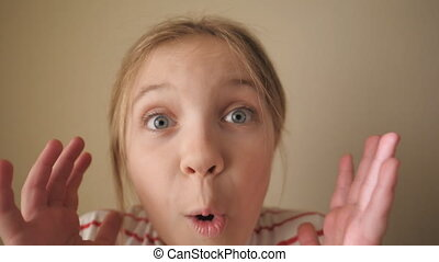Happy little blonde girl looking into camera with wow expression indoor. Portrait of beautiful child showing surprise and amazement. Close up shocked female face of small kid inside. Slow motion.