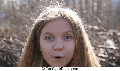 Happy little blonde girl looking into camera with wow expression outdoor. Portrait of beautiful child showing surprise and amazement. Close up shocked female face of small kid outside. Slow motion