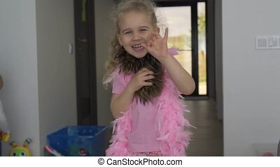 Happy little blonde girl wave hand and dance in front of...