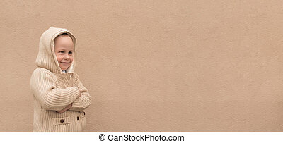 Happy little boy 3-5 years old, standing in warm beige sweater with hood, free space for text. Background wall, having fun playing joyful and smiling. Emotions of new year and holiday.