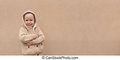 Happy little boy 3-5 years old, warm beige sweater with hood, free space text. Emotions of joy, happiness, delight pleasure, new year holiday. Background wall, having fun playing joyful and smiling.