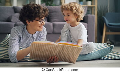 Happy little boy and his mom reading book and talking on blanket in apartment
