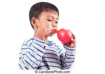 happy little boy blowing balloon