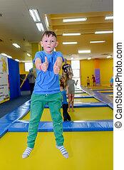 Happy little boy bouncing on a trampoline