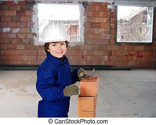 Happy little boy bricklayer