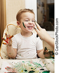Happy little boy doing finger painting sitting with his...