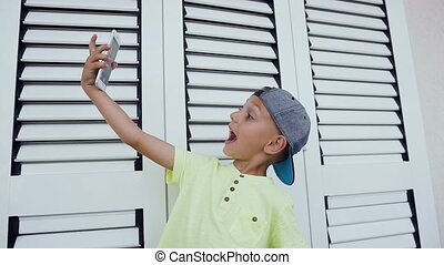 Happy little boy doing selfie photo with smartphone at home isolated on white background. Happy teenager making selfie photo for social networks