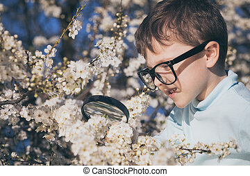 Happy little boy exploring nature with magnifying glass at the day time