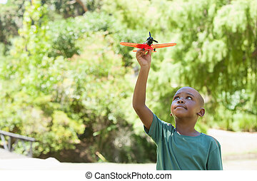 Happy little boy flying toy airplane