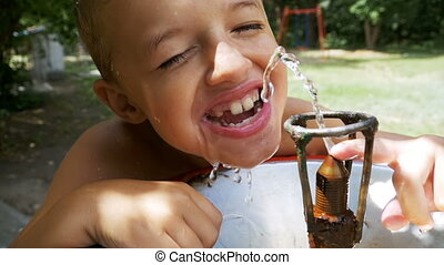 Happy Little Boy Funny Drinking Water from a Drinking Fountain on the Playground in Slow Motion