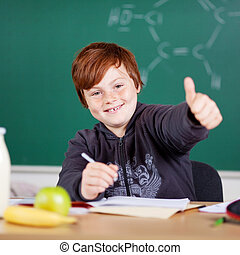 Happy little boy giving a thumbs up gesture of success while...