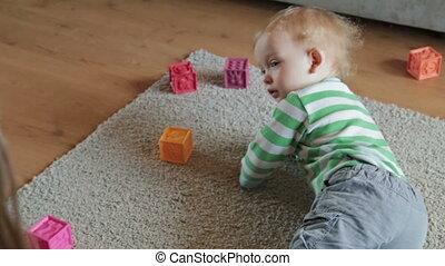 Happy little boy having fun on the floor