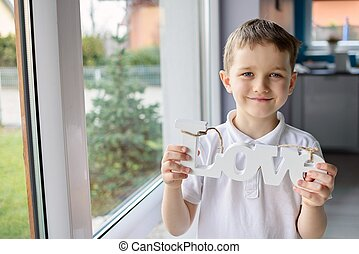 """Happy little boy holding a wooden inscription with the word """" love"""""""