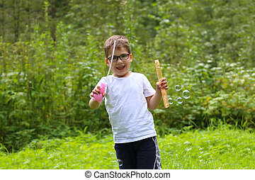 Happy little boy in glasses plays with soap bubbles in summer forest