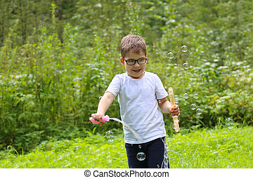 Happy little boy in glasses plays with soap bubbles in summer green forest