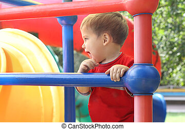 Happy little boy in red T-shirt playing on playground