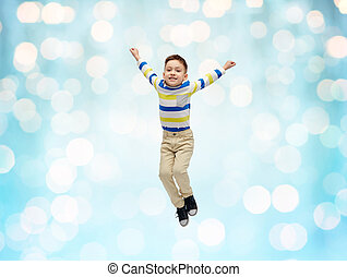 happy little boy jumping in air over blue lights