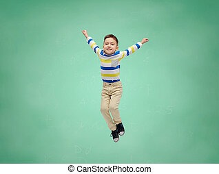 happy little boy jumping in air over school board