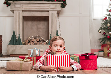 boy laying on floor with christmas gifts