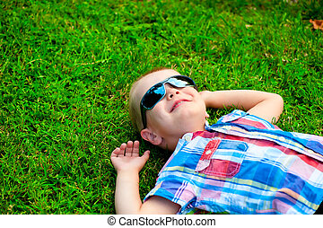 happy little boy lying down resting on the green grass in sunglasses