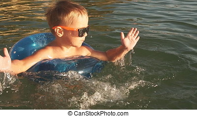 Happy little boy making splashes in water. Child having fun in sea at Sunset.