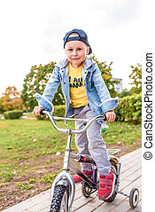 happy little boy of 3-5 years old, in summer in city park, smiles rejoices, is learning to ride a bicycle, learns how Autumn clothes. Emotions of pleasure and relaxation.