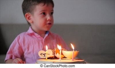 Happy little boy of four sits on the couch looking at the burning candles on the birthday cake, makes a birthday wish, celebrates the birthday with his family, and blows out the candles on the cake.