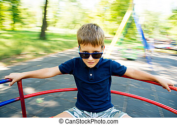happy little boy on the carousel on playground