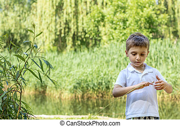 Happy little boy playing at the pond in the city park on a summer sunny day. Close up. Beautiful summer background with copy space