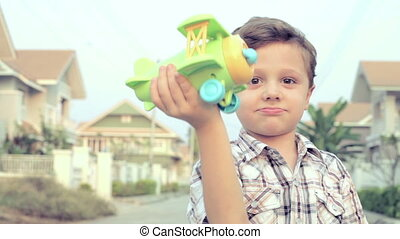 happy little boy playing near a house