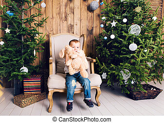 Happy little boy playing near the Christmas tree