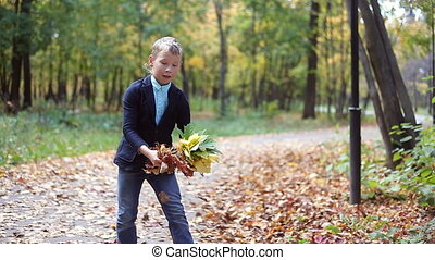 Happy little boy playing with autumn leaves in the woods