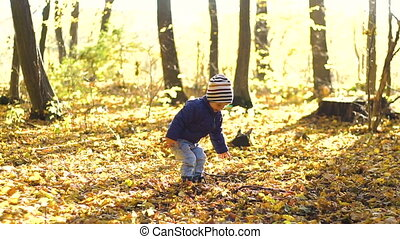 Happy little boy playing with autumn leaves throwing leaves in slow motion