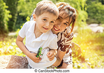 Happy little boy playing with his mother in the city park on a summer sunny day. Mother and son in the park near pond.