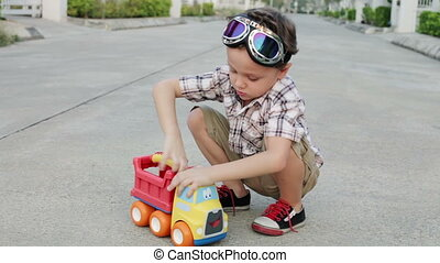 Happy little boy playing with toy car