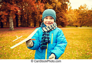 happy little boy playing with toy plane outdoors