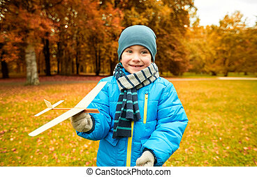 happy little boy playing with toy plane outdoors - autumn,...