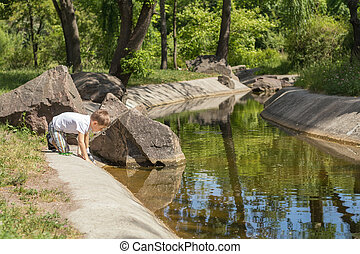 Happy little boy playing with water at the pond in the city park on a summer sunny day. Close up. Beautiful summer background with copy space