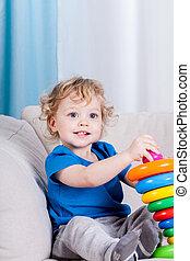 Happy little boy plays with blocks